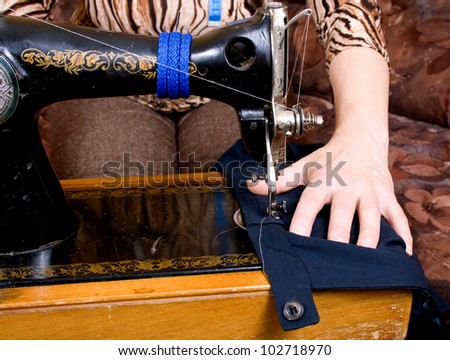 Hands of a seamstress at the sewing machine