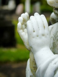 Hands of a white statue in an almost prating position