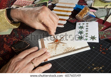 Hands of a woman crafting and scrap-booking christmas cards