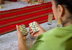 Hands of a woman holding with both hands dominoes game tokens