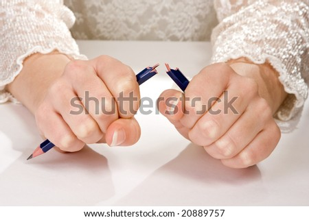 Hands of a woman in stress, breaking a pencil