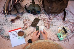 Hands of a woman planning vacation trip on a world map checking passport and travel accessories - freedom concept