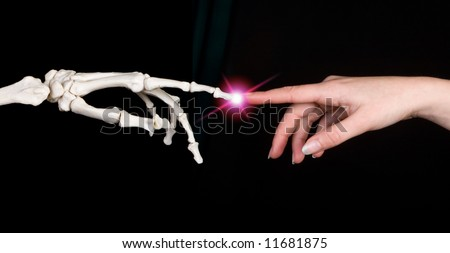 Hands of a woman touching the hand of a skeleton