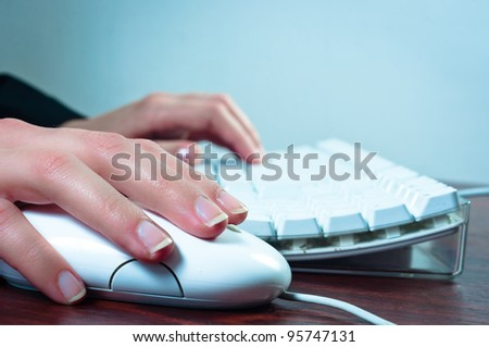 Hands of a woman using mouse and keyboard