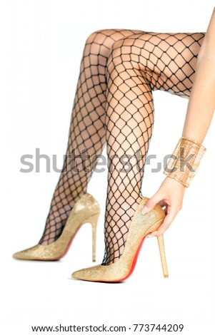 0132d2c6194 hands of a woman while putting golden high heels shoes on