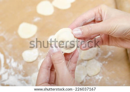 Hands of a woman who molds dumplings on kitchen table