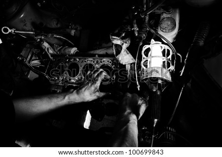 Hands of a worker repairing car motor