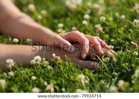 hands of a young couple lying on grass in park