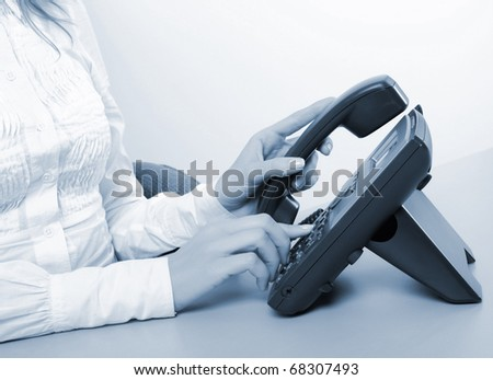 Hands of a young girl on the phone dials the number
