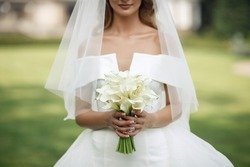 Hands of a young girl with a beautiful manicure and rings hold of fresh white calla lilies. The bride in a white dress holds a classic wedding bouquet
