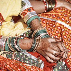 Hands of a young Indian woman adorned with traditional bangles and mehndi. Mehandi, also known as henna is a temporary form of skin decoration in India.