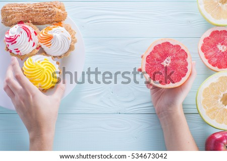 Hands of a young woman holding a grapefruit. Woman making a choice between cake and fruits, made a choice in favor of fruits and holding half a grapefruit. Unhealthy vs healthy food, top view.