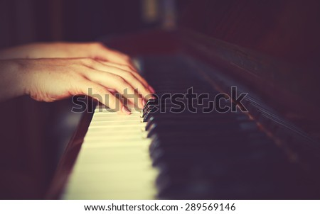 hands of a young woman pianist on the piano keyboard