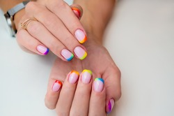 Hands of a young woman with a manicure. The nails are covered with gel polish with colored French.