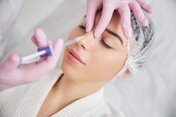 Hands of aesthetic master accurately applying hyaluronic acid in woman nose