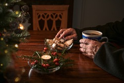 Hands of an elderly lonely man on a table with Christmas cookies, coffee and festive decoration next to an empty chair, sad holidays during the croronavirus pandemic or after a loss