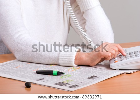 hands of an elderly woman calling on the phone by newspaper ad