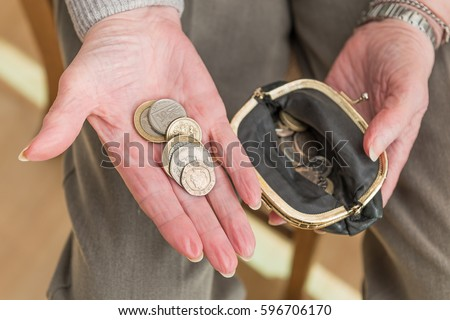 Hands of an elderly woman with British money in the palm of her hand and an open purse containing coins.