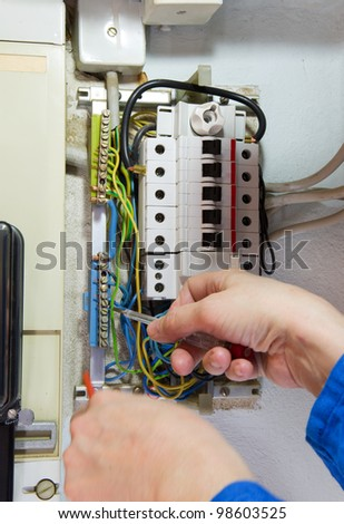 hands of an electrician measuring electrical cables - stock photo