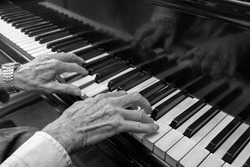 Hands of an old musician playing music on the keyboard of a grand piano, black and white image, concept for culture, art and entertainment, copy space, selected focus, narrow depth of field