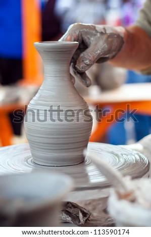 Hands of an old potter making a flower vase out of earth