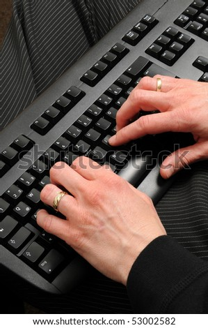 Hands of an older woman on a computer keyboard