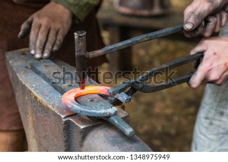 Hands of an unidentified, unrecognizable blacksmith, who forges a horseshoe. Vintage smith craft technology. History of human civilization
