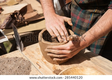 Hands of an unrecognizable male potter, ceramist in making of an earthenware pot