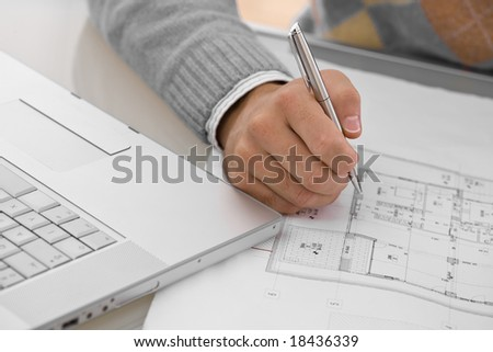Hands of architect drawing blueprint at desk.