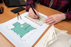 Hands of architect during work. Concept - work in an architectural bureau. Architect career. Man draws construction drawings. Apartment plan on paper. Career in architectural business.
