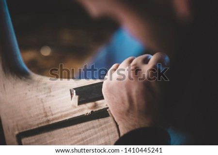 hands of artisan luthier sanding, building a double bass