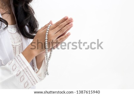 Hands of Asian muslim woman wearing prayer beads welcoming guests / Ied Fitr Greeting in white background  #1387615940
