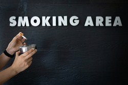 Hands of asian woman holding a ashtray and cigarette,people extinguishing a cigarette in smoking area zone,designated smoking area text on black background,unhealthy lifestyle,quit smoking concept