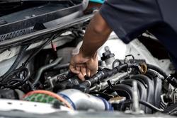 Hands of auto mechanic repairing car engine in garage. Maintenance car.