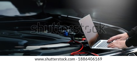 Hands of auto mechanic using computer for diagnostics engine working and repairing car in a garage. Blur repair service in background. wide panoramatic banner with empty space for copy text. Foto stock ©