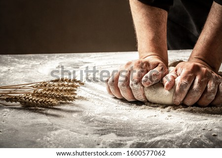 Hands of baker kneading dough isolated on black background. prepares ecologically natural pastries. ストックフォト ©