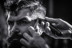 Hands of barber with hair clipper. Barber works with hair clipper. Hipster client getting haircut. Haircut concept. Man visiting hairstylist in barbershop. Black and white.