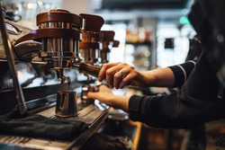 Hands of barista making coffee in bar