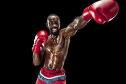 Hands of boxer over black background. Strength, attack and motion concept. Fit african american model in movement. Afro muscular athlete in sport uniform. Sporty man during boxing