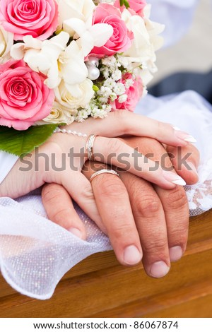 Hands of bride and groom and rings with wedding bouquet