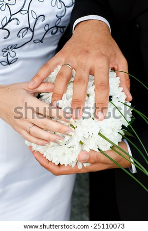 hands of bride and groom on the bouquet