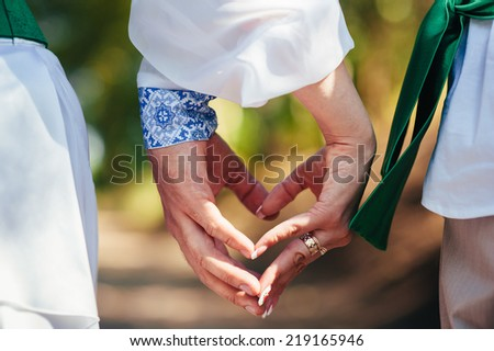 Hands of bride and groom. Ukraine. Happy ukrainian wedding (bridal) couple in the ukrainian style. Beautiful bride and groom in the ukrainian style are standing with bouquet. Female and male models.
