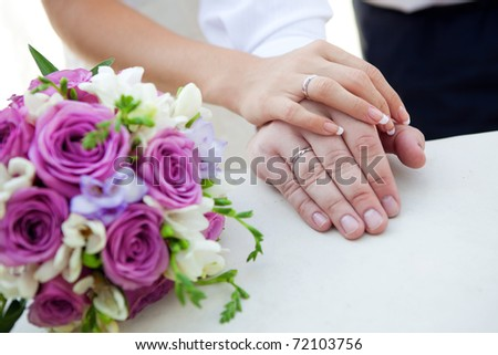 hands of bride and groom with bouquet