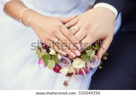 Hands of bride and groom with rings on wedding bouquet. Marriage concept.