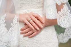 hands of bride in white dress with manicure wedding day