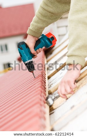 Hands of builder worker at roofing works on tiling with screwdriver