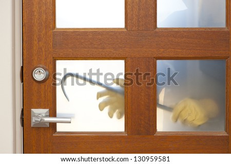 Hands of Burglar, thief  with gloves, holding crowbar trying to break in home, unlock door, blurred visible silhouette behind milky windows, with copy space.