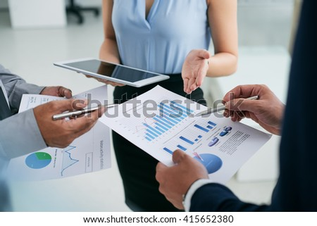 Hands of business executives discussing financial reports