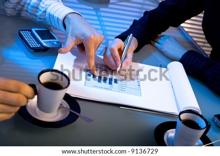Hands of business people pointing at graph on table. Night time, indoor.