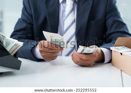 Hands of businessman counting dollar banknotes